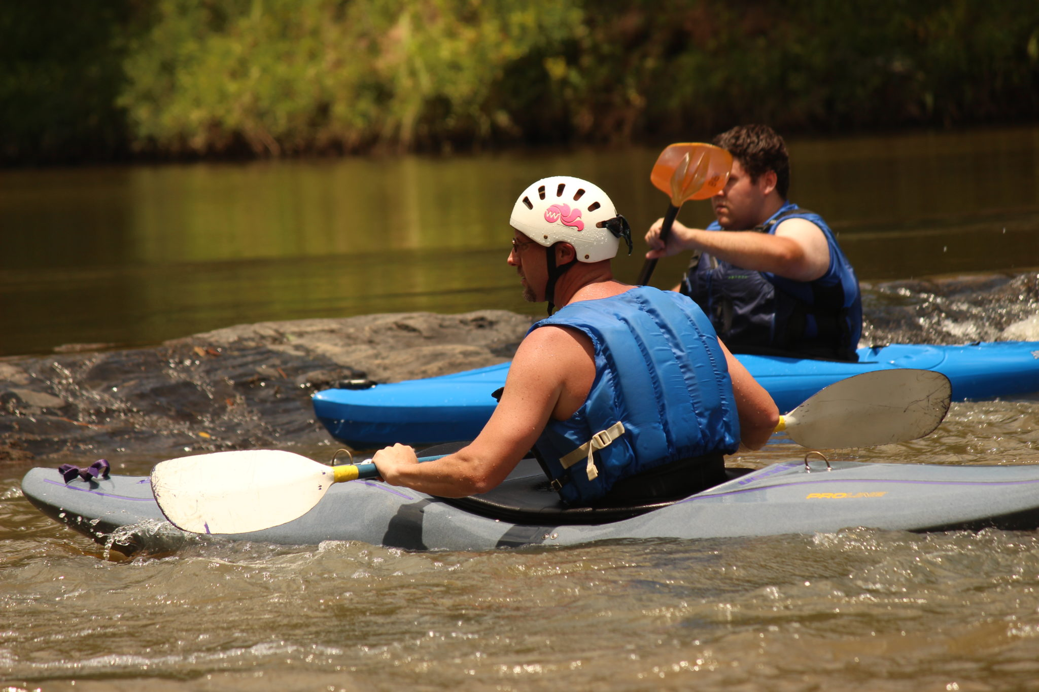 Friends kayaking down a river in Villa Rica, GA